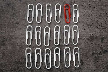 One red clip among white ones on gray background. Difference and uniqueness concept