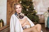 Fiatal nő aranyos mopszli kutya otthon. Kisállat Örökbefogadás