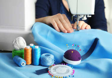 Close up of woman sewing on machine with blue fabric and colorful threads