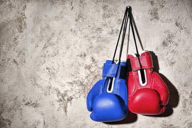 Red and blue boxing gloves hanging on wall. Concept of political confrontation between American major parties - Democratic and Republican