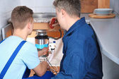 Photo Plumber with young trainee repairing sink in kitchen