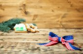 Photo American flag bow and confetti on wooden table. USA holiday