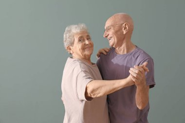 Cute elderly couple dancing against color background