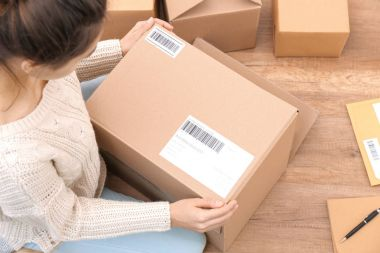 Female startupper preparing parcels for shipment to customers indoors