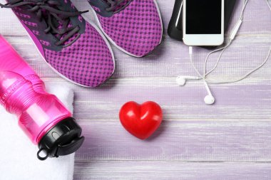 Gym stuff, phone and red heart on wooden background. Cardio training concept