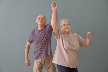 Cute elderly couple dancing against color background