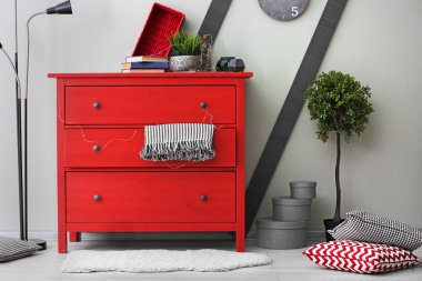 Cozy wardrobe room interior with red chest of drawers
