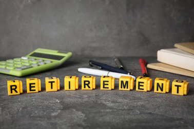 Word retirement on dark table, pension planning