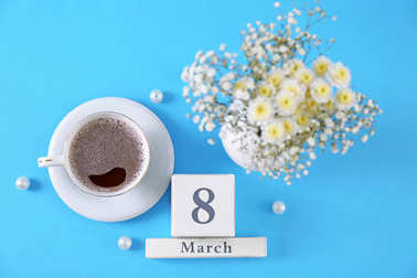 Wooden block calendar, cup of coffee and flowers on color background. International Women's Day celebration