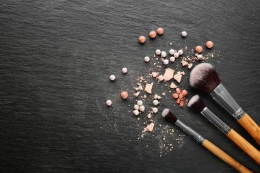 Brushes with crushed decorative cosmetics  of professional makeup artist on dark background