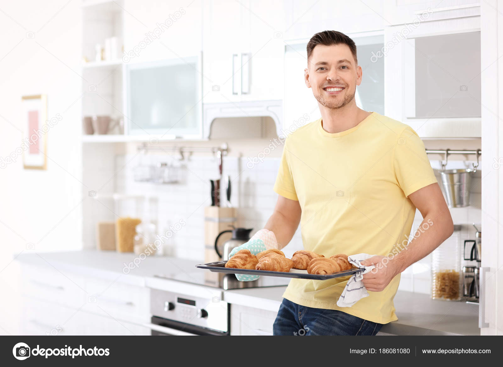 Man holding baking tray with delicious homemade croissants in ...