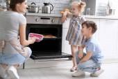 Fotografie Kleine Kinder beobachten ihre Mutter Kekse im Ofen Zuhause backen