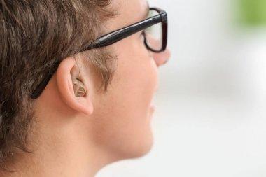 Teenage boy with hearing aid indoors