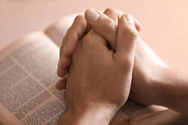 Male hands folded in prayer over open Bible, closeup