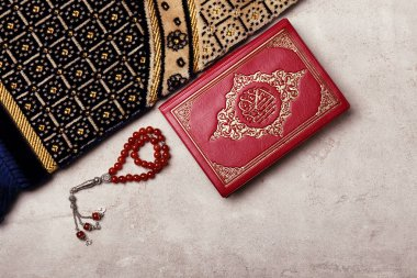 Holy book of Muslims, prayer beads and rug on gray background