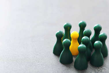 Yellow pawn among green ones on gray table. Difference and uniqueness concept
