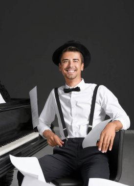 Young man sitting near piano with flying music sheets indoors