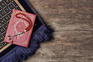 Holy book of Muslims, prayer beads and rug on wooden background