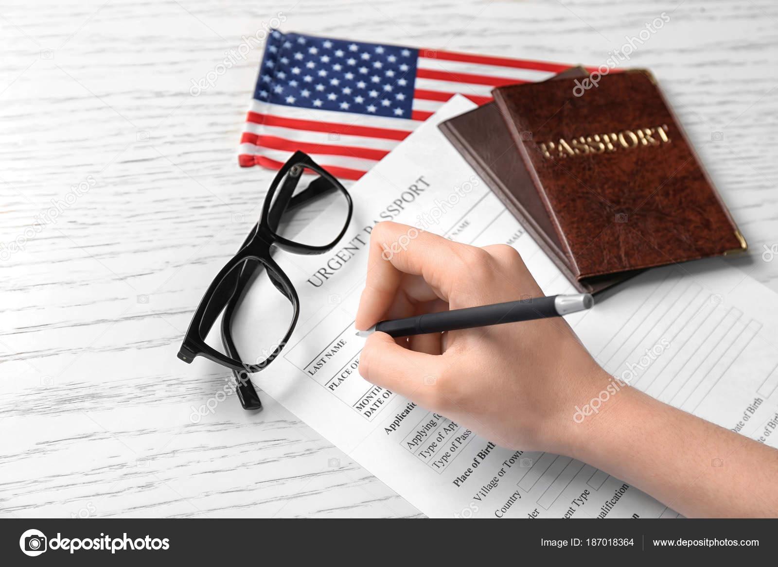 Woman filling urgent passport application form near american flag woman filling urgent passport application form near american flag at table immigration to usa falaconquin