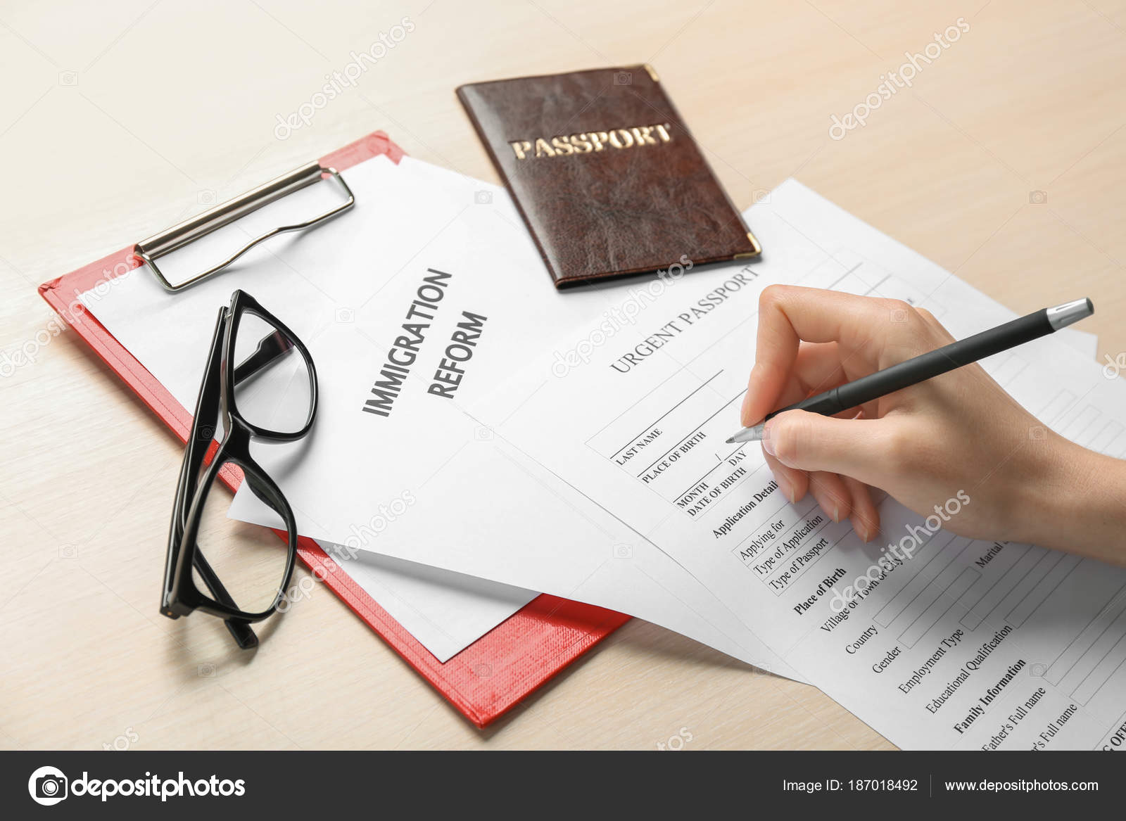 Woman filling urgent passport application form at table woman filling urgent passport application form at table immigration and citizenship stock photo falaconquin
