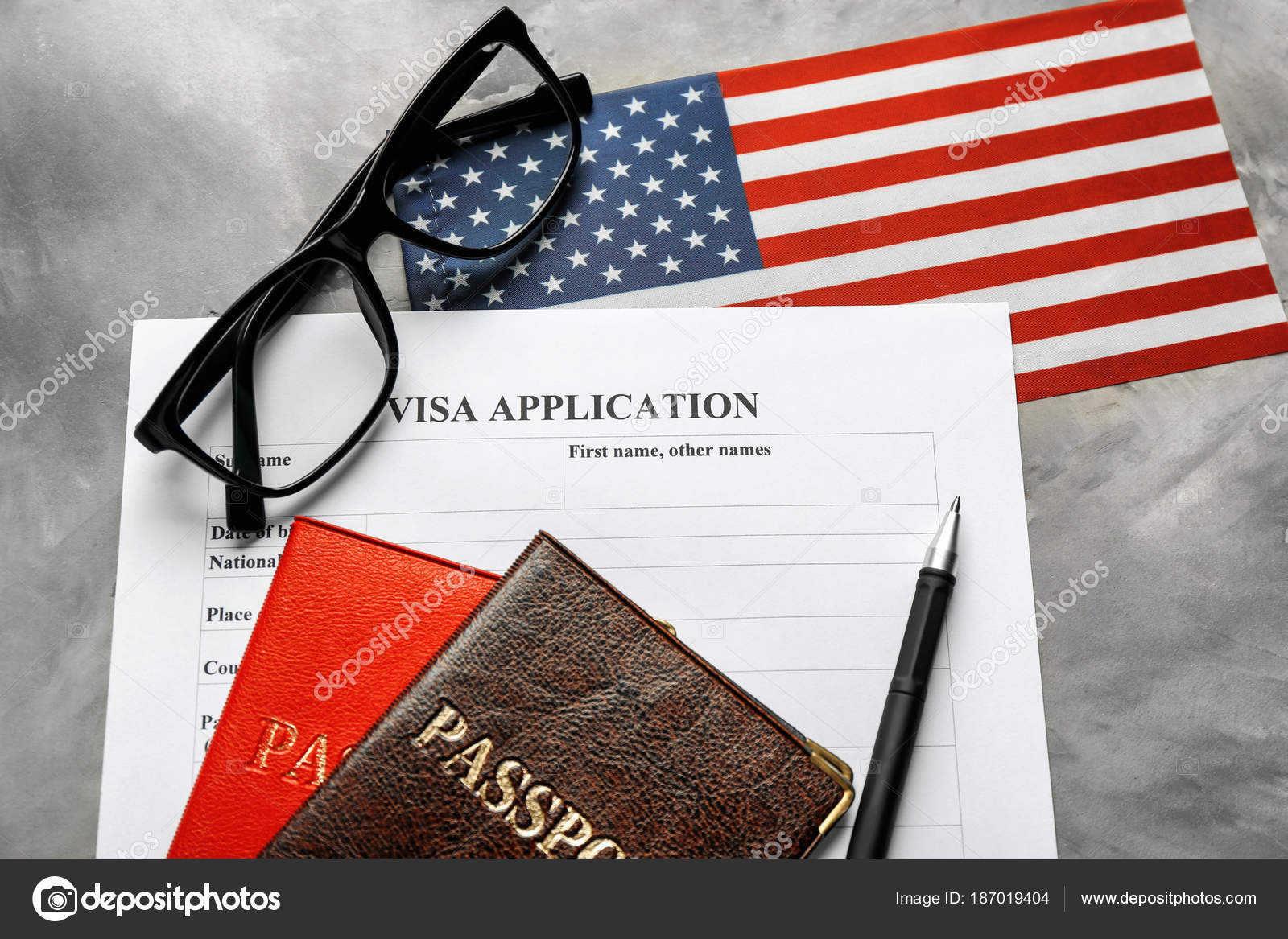Passports, American flag and visa application form on table
