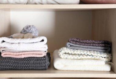 Warm hats and scarves on shelf of wardrobe closet