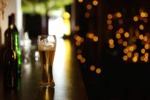 Fotografia Vetro di birra sul tavolo contro sfondo sfocato