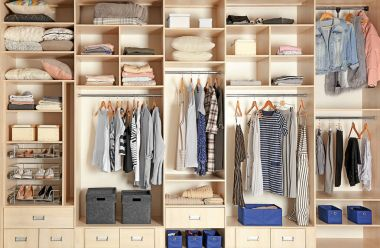Large wardrobe closet with different clothes, shoes and home stuff