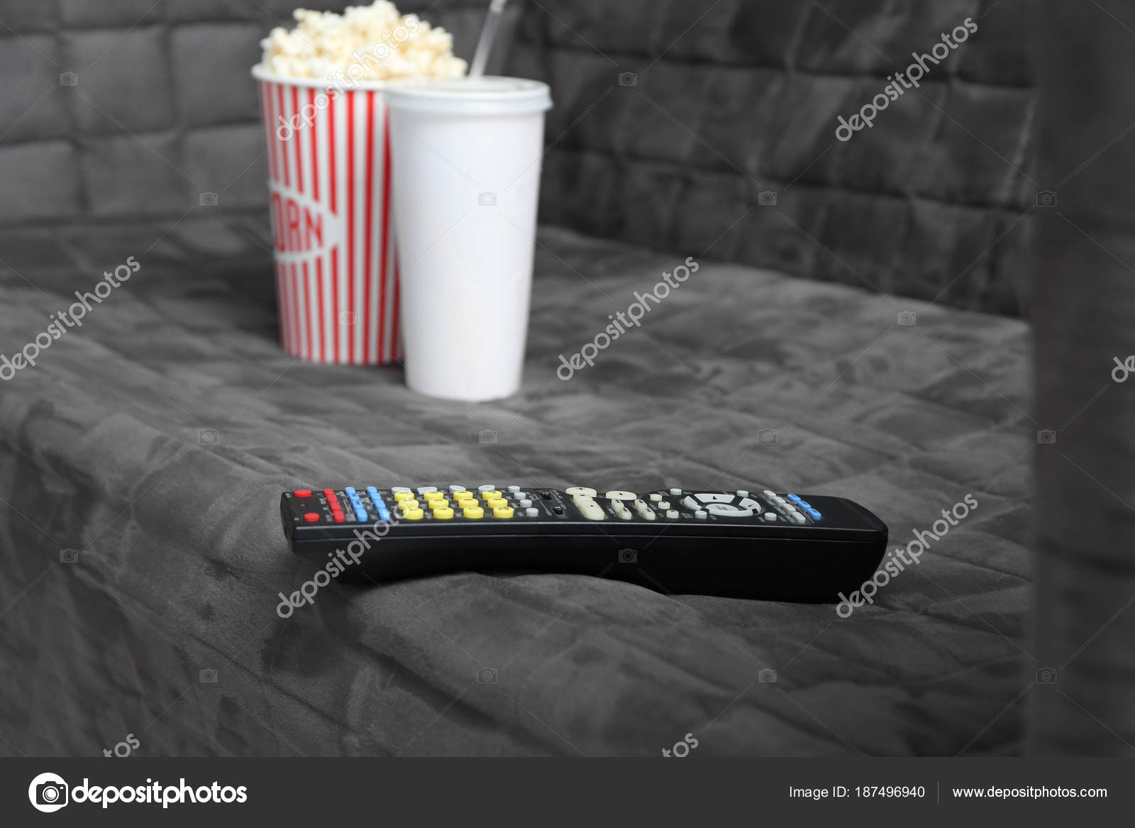Comfortable sofa with TV remote control and snack, closeup  Home