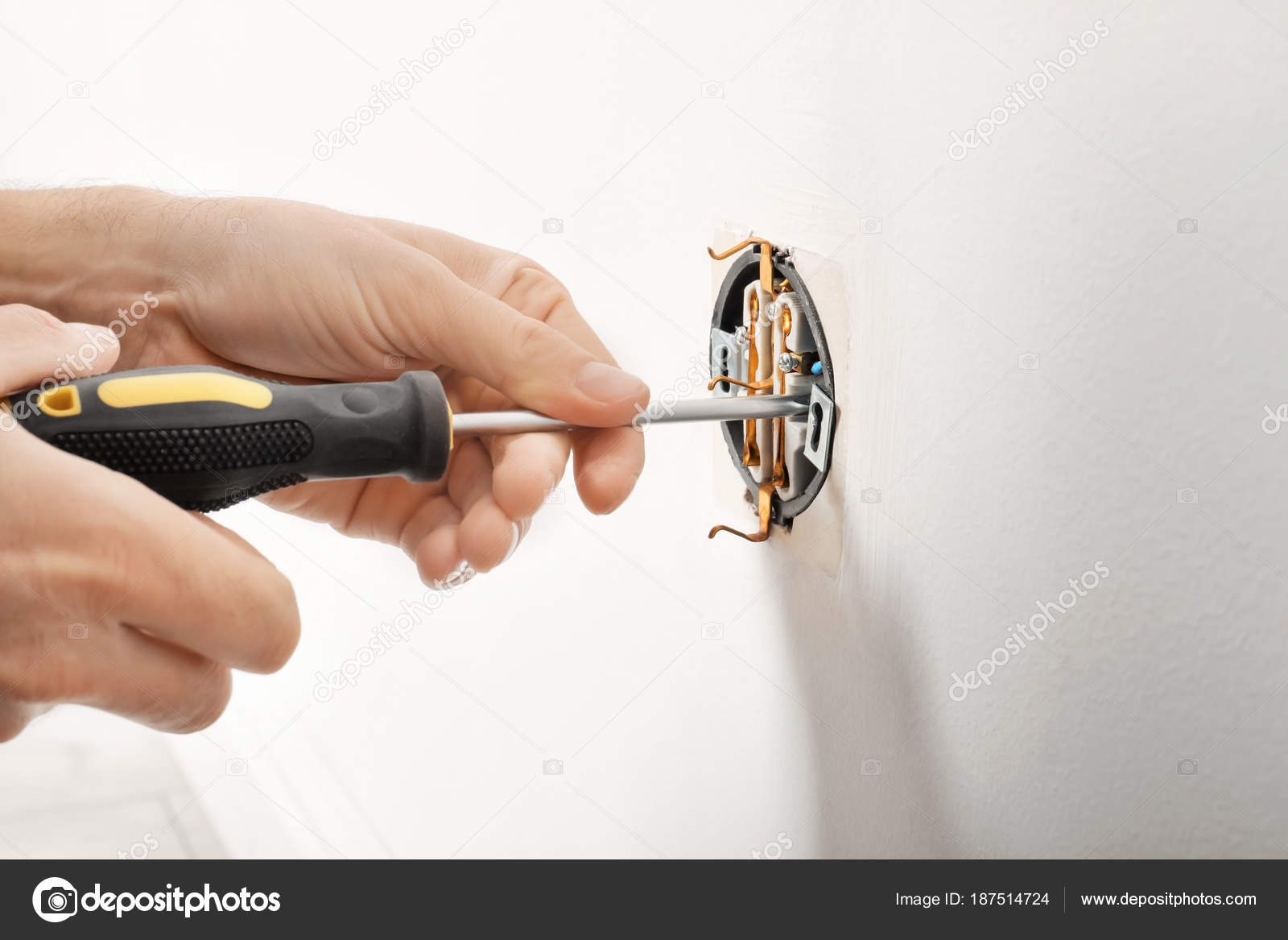 Electrician repairing socket on light wall — Stock Photo