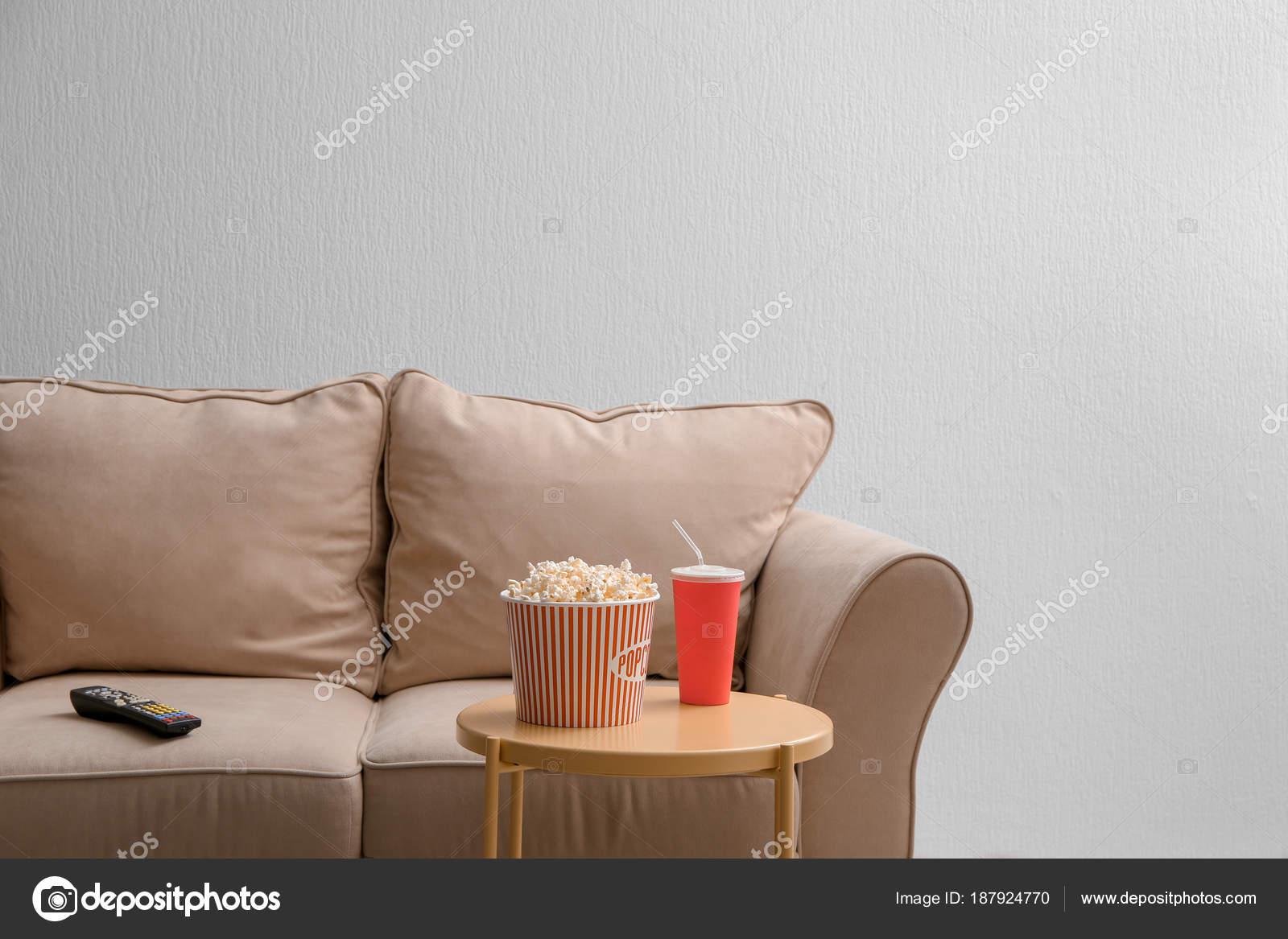 sofá confortável com controle remoto de tv e lanche na mesa dentro