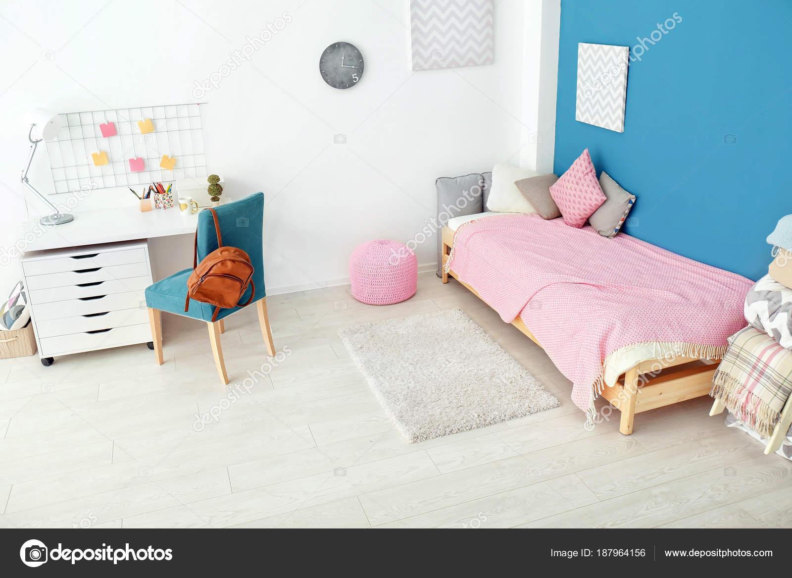 Interieur van gezellige kinderkamer met tafel en comfortabele bed