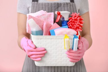 Woman holding basket with cleaning supplies