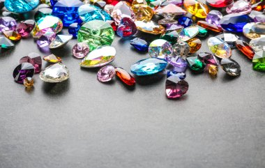 Colorful precious stones for jewellery on grey background