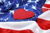 Fotografie Red felt heart on American flag. USA holiday