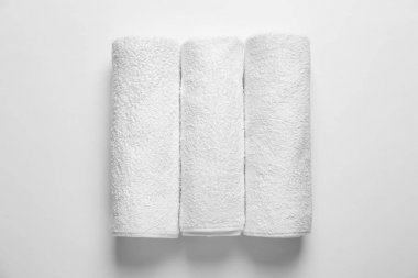 Rolled clean terry towels on white background, top view