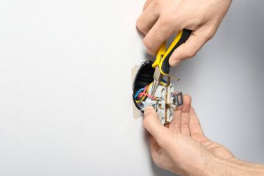 Electrician repairing socket on light wall