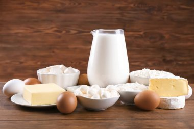 Different dairy products and eggs on wooden table
