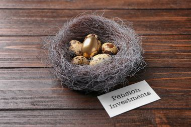 Nest with eggs and sign PENSION INVESTMENTS on wooden background