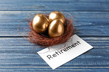 Golden eggs in nest and sign RETIREMENT on wooden background. Pension planning