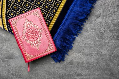 Holy book of Muslims and prayer rug on gray background
