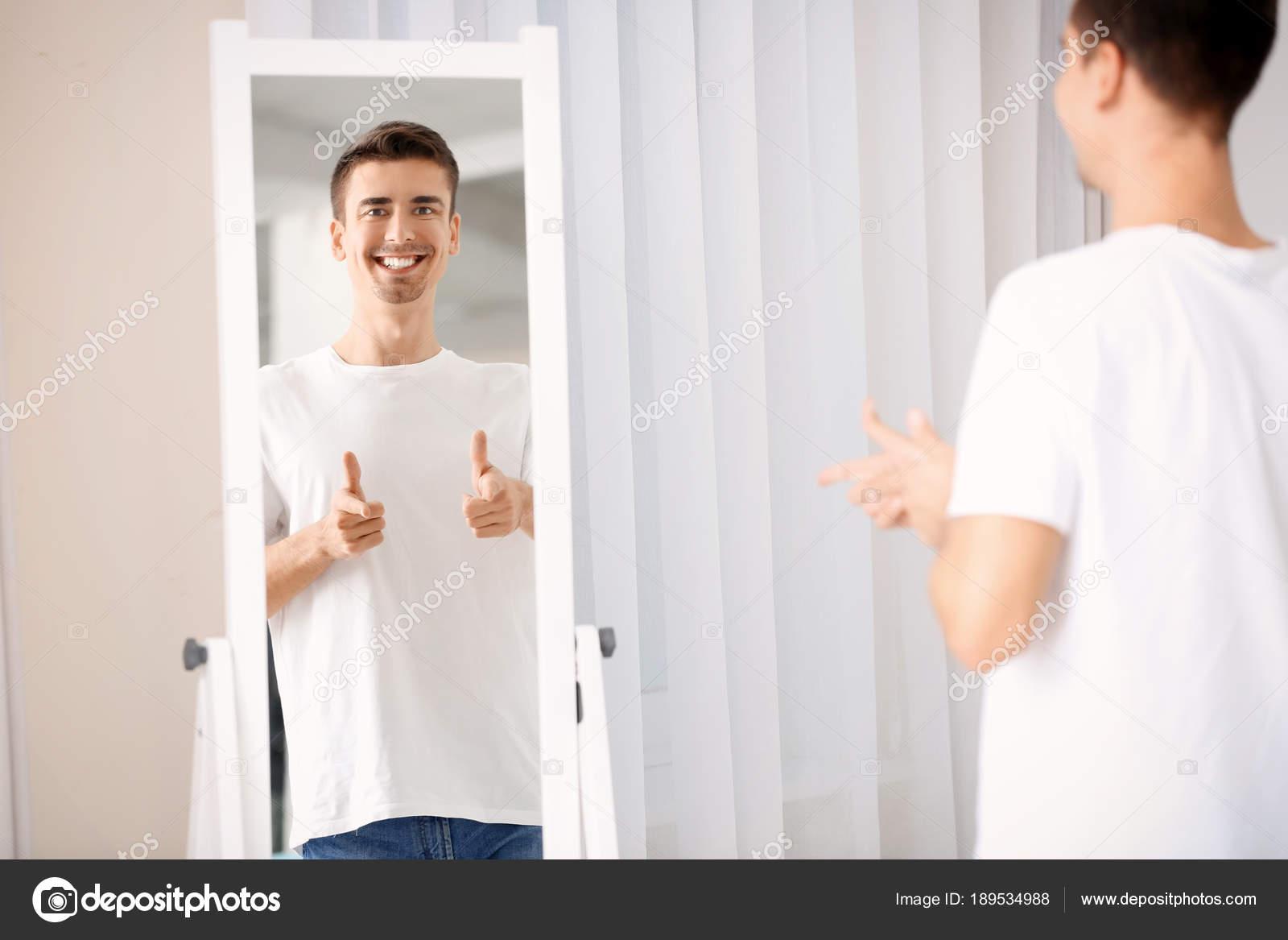 handsome man looking in mirror stock photo belchonock 189534988