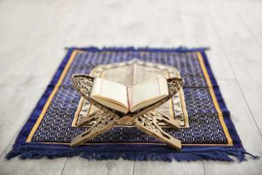 Opened Quran on Muslim prayer mat indoors