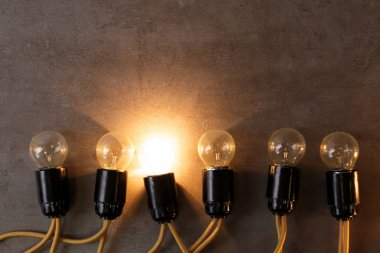 Unique glowing light bulb among switched off ones. Individuality and leadership concept