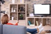 Nő néz Tv közben pihen a kanapén, otthon