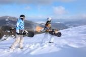 Fotografie Paar mit Snowboards auf Skipiste im verschneiten Resort. Winterurlaub
