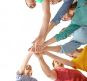 Fotografie Junge Menschen setzen Hände zusammen auf hellem Hintergrund. Einheit-Konzept