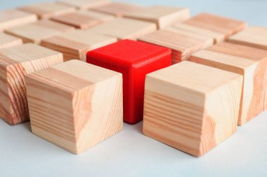 One red cube among wooden ones on table. Difference and uniqueness concept