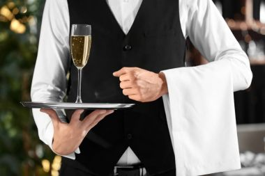 Waiter holding tray with glass of champagne in restaurant