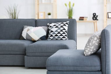 Modern grey sofa with different pillows in living room